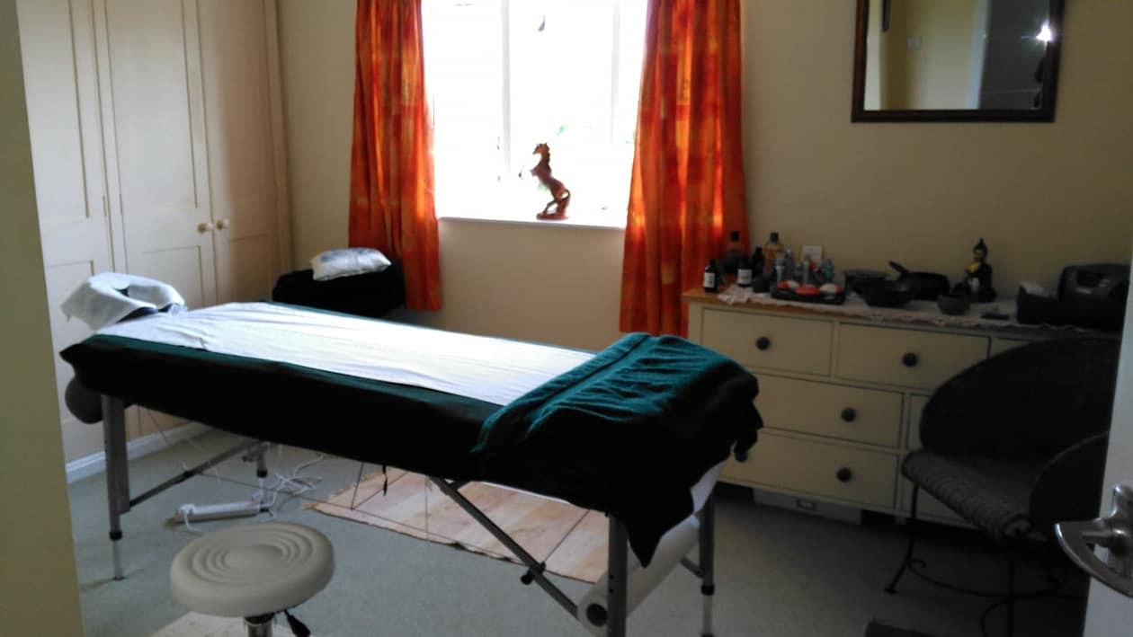 massage bench in studio - large window,  with iron leaping horse sculpture on window sill.